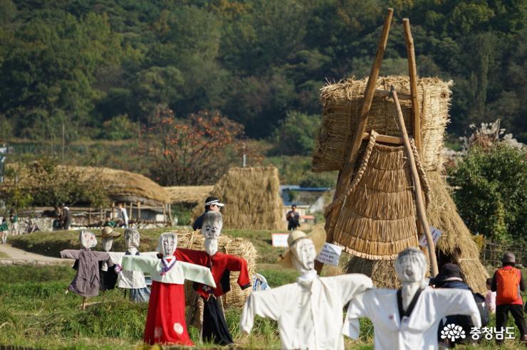 마을 입구에 장식된 허수아비와 풍요를 상징하는 거대한 쌀가마 지게.